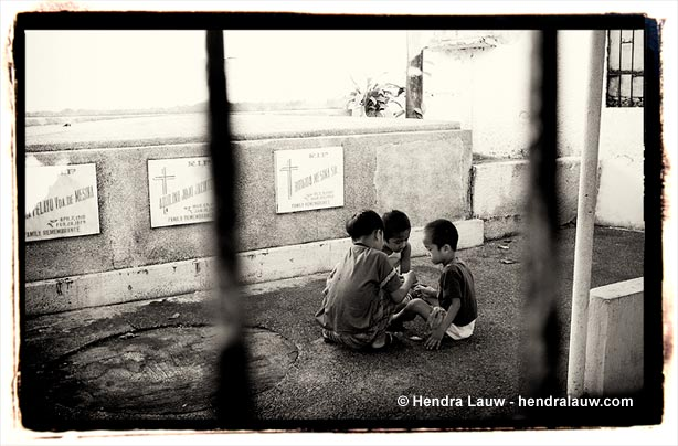 Three boys playing at Manila North Cemetery