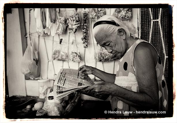 An old woman reading newspaper at the Manila North Cemetery