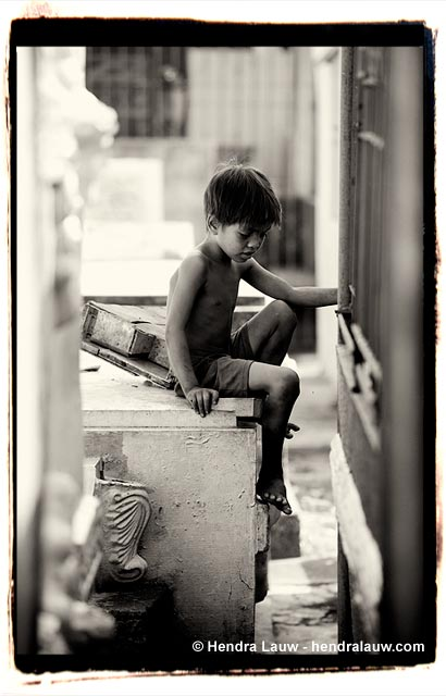 A boy playing alone at the Manila North Cemetery