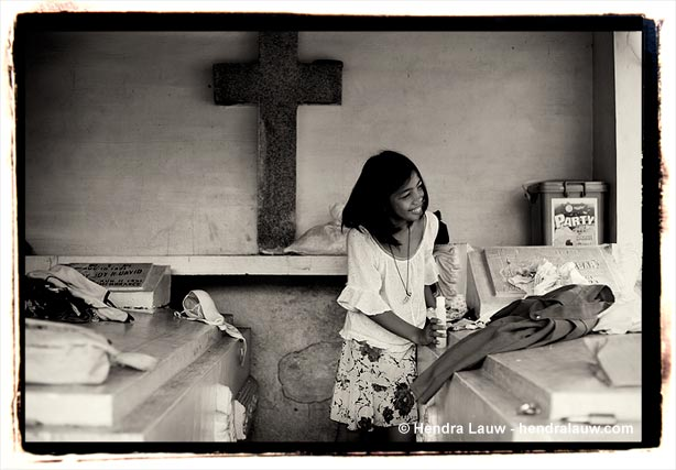 Folding clothes at the Manila North Cemetery