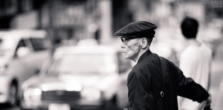 An old man waiting to cross the Possession Street
